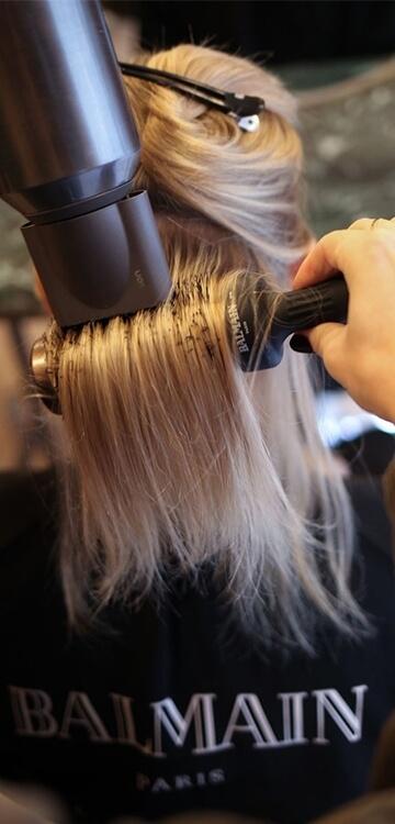 Frisør på Frederiksberg føntørrer hår på kunde ved håropsætning